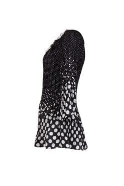 Kriss Tunika Pari. svart vit plisserad tunika med rund halsringning och vita blommor som halsbrodyr.
