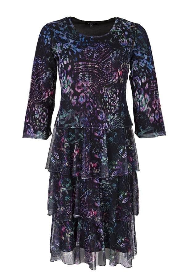 Vacker klänning Vivienne i mesh med printade blommor, i färgerna svart, grönt och lila. Klänningen har ett snyggt fall med volanger och är fodrad.
